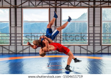 Two men in sports wrestling tights and wrestling during a traditional Greco-Roman wrestling in fight on a wrestling mat against the backdrop of mountains. Wrestler throws his opponent's chest through