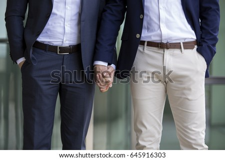 two men in suits standing and holding hands #645916303