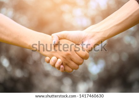 Two men join hands to show unity. #1417460630