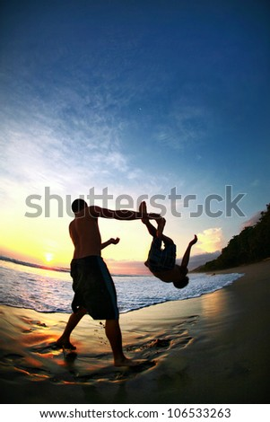 Two Men Jump In Pacific Ocean During Sunset - stock photo