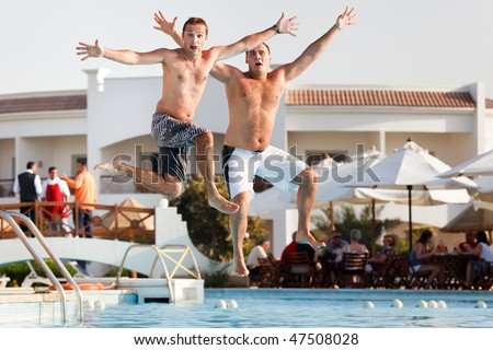Two men jumping in swimming pool.  Low angle view from the swimming pool.