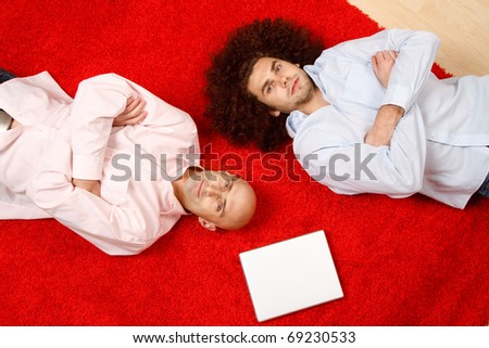 Two men laying side by side on their backs on a red rug in opposite directions, with their arms crossed in front of them.  A blank white paper is on the rug near them.