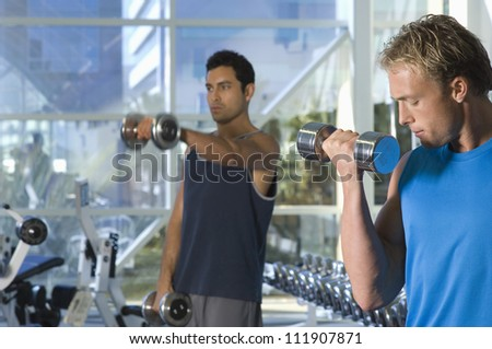 Two men lifting weights at a gym