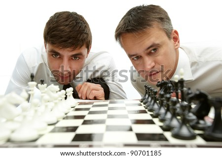 Two men looking at chess figures on chess board