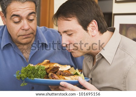 Two men looking at plate of food - stock photo