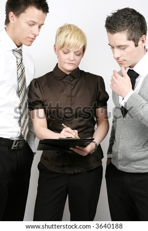 Two men looking at the businesswoman writing the contract