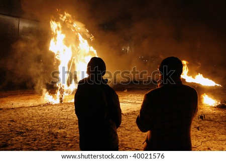 Two men looking at the fire