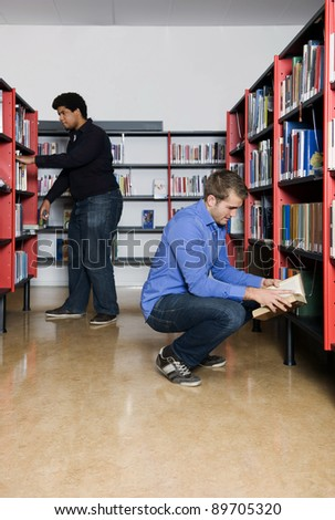 Two men, looking throught the books in bookselves at a public library