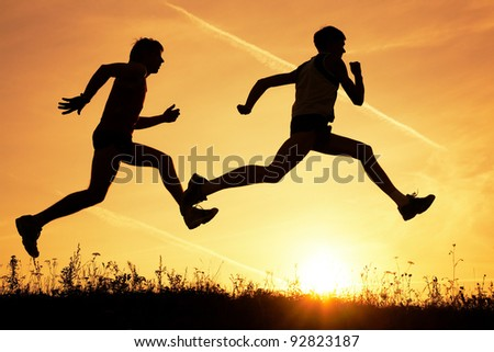 Two men make jog in the field on a sky background by at sunset