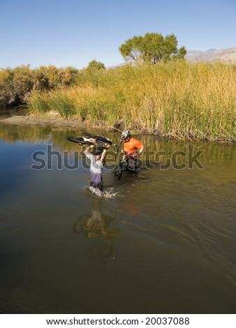 Two men mountain biking having to cross a river in the foothills of the Sierra Nevada Mountains, California, on a sunny day.