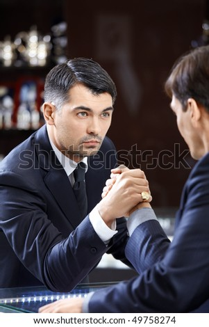 Two men of average years in suits have crossed hands