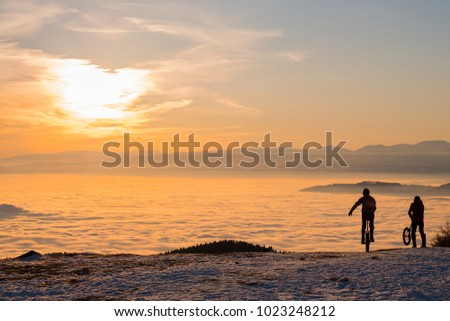 Two men on unicycles riding on snowy mountain Schoeckl in Styria, Austria over low stratus fog to sunset #1023248212