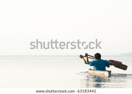 two men paddling in a canoe at the sea of Galilee