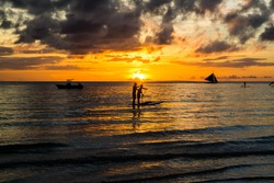 Two men paddling their boards of into the sunset in the island of Boracay,Philppines