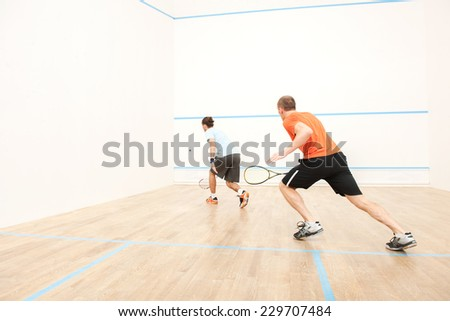 Two men playing match of squash. Back view of squash player in action reaching on squash court  ストックフォト ©