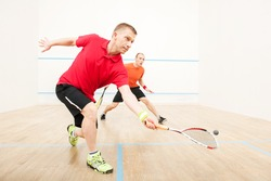 Two men playing match of squash. Closeup of squash players in action on squash court