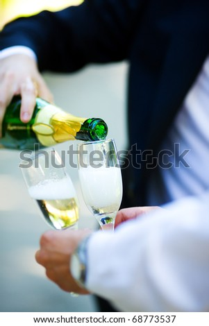 Two men pouring Champagne outdoors hands closeup
