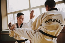 Two men practicing taekwondo together in the gym. People stand in the hall and practice martial arts techniques.