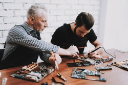 Two Men Repairing Hardware Equipment from PC. Repair Shop. Worker with Tools. Computer Hardware. Young and Old Workers. Soldering Iron. Digital Device. Laptop on Desk. Electronic Devices Concept.