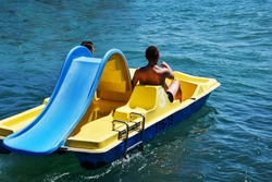 Two men ride a yellow catamaran in the sea. Friends pedal and row, so the catamaran moves away from the shore. The concept of male friendship, love, lgbt. Romantic sailing of two men on a catamaran