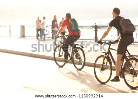 two men ride bicycles on the summer sunny city embankment