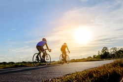 Two men ride on bike on the road. Sport and active life concept sunset time. Couple of men riding on  bicycle in a park. Blue sky with orange sun beam over the body of cyclist.