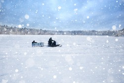 Two men riding on a snowmobile winter river.