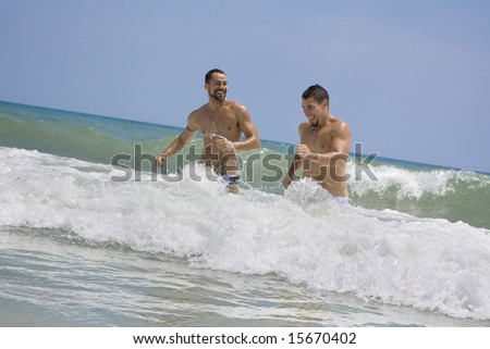 Two men running in the ocean