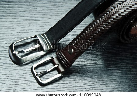 Two men's belts on grey background.