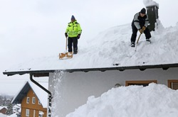 Two men shoveling high heavy snow from a house roof