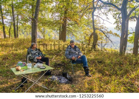 Two men sit at a table on a halt in the autumn forest near the fireplace.