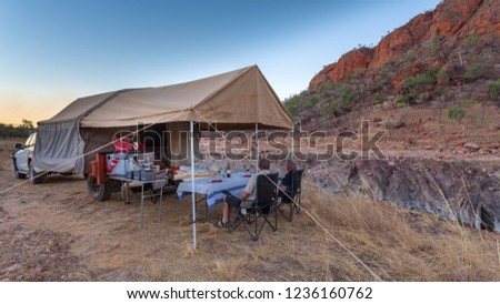 Two men sitting and enjoying a wine outside a off road camper set up alongside a small gorge and mountain in the Kimberley of Western Australia.