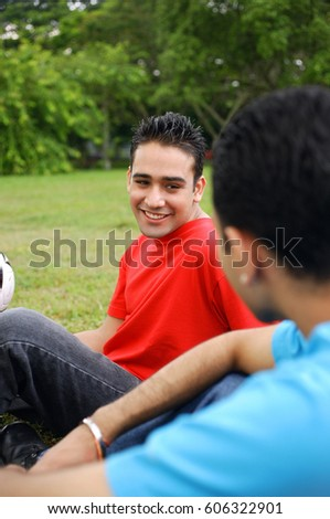 Two men sitting on grass, side by side #606322901