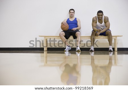 Two men sitting on sidelines of basketball court