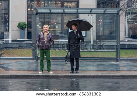 Two men stand at the bus stop, one of them is sad, another is cheerful, it's raining, one of them with an umbrella