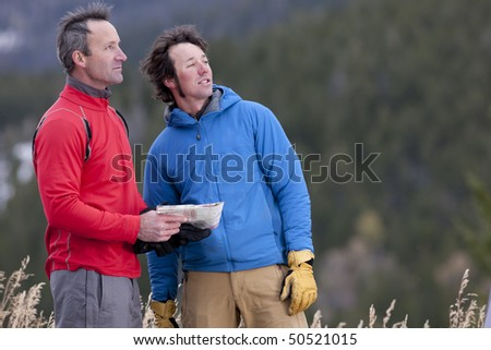 Two men stand together in a clearing in the wilderness and look out into the distance. One is holding a map. Horizontal format.