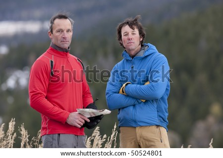 Two men stand together in the wilderness and look at the camera with serious expressions. One is holding a map. Horizontal format.
