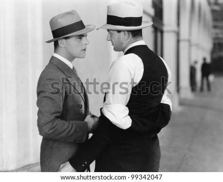 Two men standing together talking - stock photo