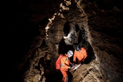 Two men, strong physique, explore the cave. Men dressed in special clothes to pass through the cave and stopped, looking at the map.