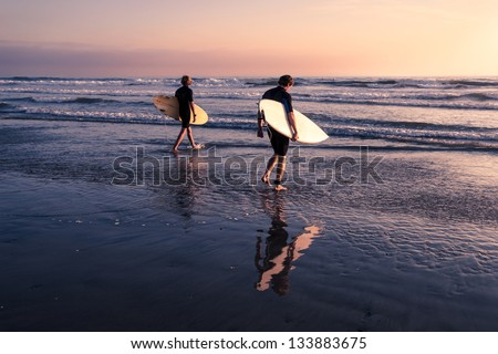 Two Men - Surfers in black diving suits. With old white and yellow surfboards. On the beach at sunset. #133883675