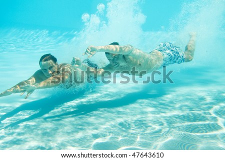 Two men swimming with open eyes underwater in pool