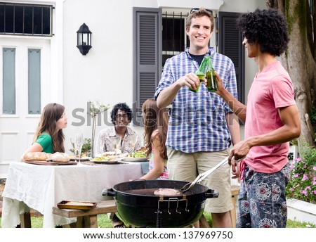 Two men toasting beers by the barbeque at a party, with meat on the smoking grill