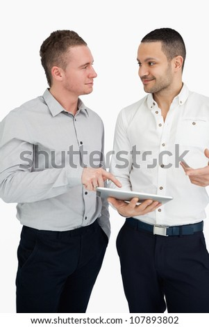 Two men together while holding a tablet computer against a white background