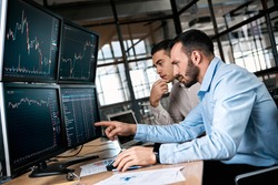 Two men traders sitting at desk at office together monitoring stocks data candle charts money flow on screen concentrated teamwork discussing strategy concept