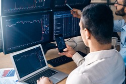 Two men traders sitting at desk at office together monitoring stocks data teamwork concept man holding smartphone browsing application looking at candlestick charts price flow online