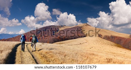Two men traveling in the mountains - stock photo
