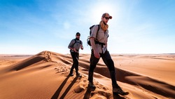 Two men trekking the Wahiba deserts in Oman.