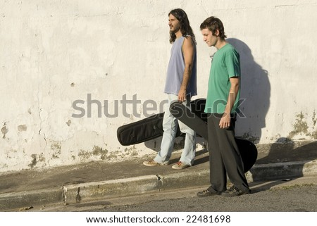 Two men walking down a street carrying guitars in guitar cases. Horizontally framed photo.
