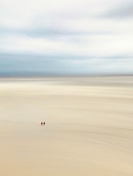 Two men walking on sand before the rising tide