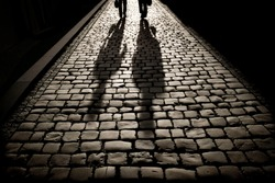 Two men walking on the pavement at the sunrise or sunset with shadow silhouettes